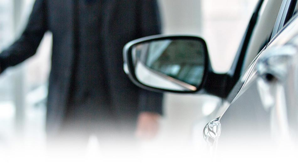 Side view mirror of a vehicle with a sales representative in the out of focus background