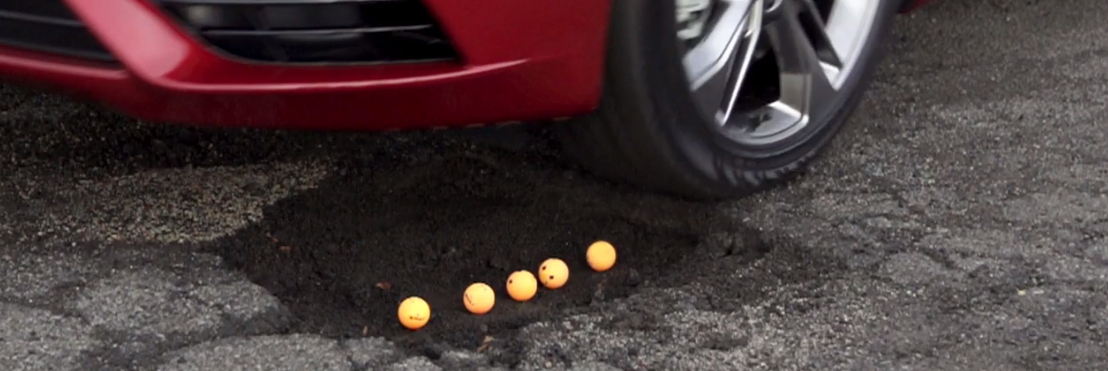 Car about to drive over pothole with ping pong balls in it.