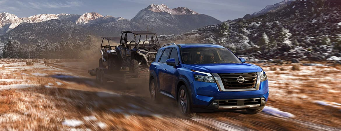 Picture of the 2022 Nissan Pathfinder, driving on terrain and towing a load.