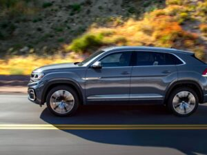 2021 Gray Atlas Cross Sport SUV driving on the road from a side perspective