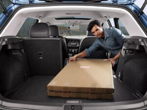 Man loading boxes into his 2021 Golf GTI by using the new rear seat pass-through feature