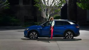 Side exterior view of a woman getting out of her Volkswagen ID4 SUV