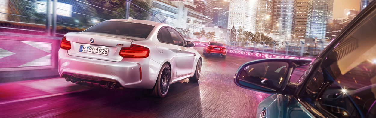 3 BMW M2 Competition models racing on a racetrack from a outside driverside view