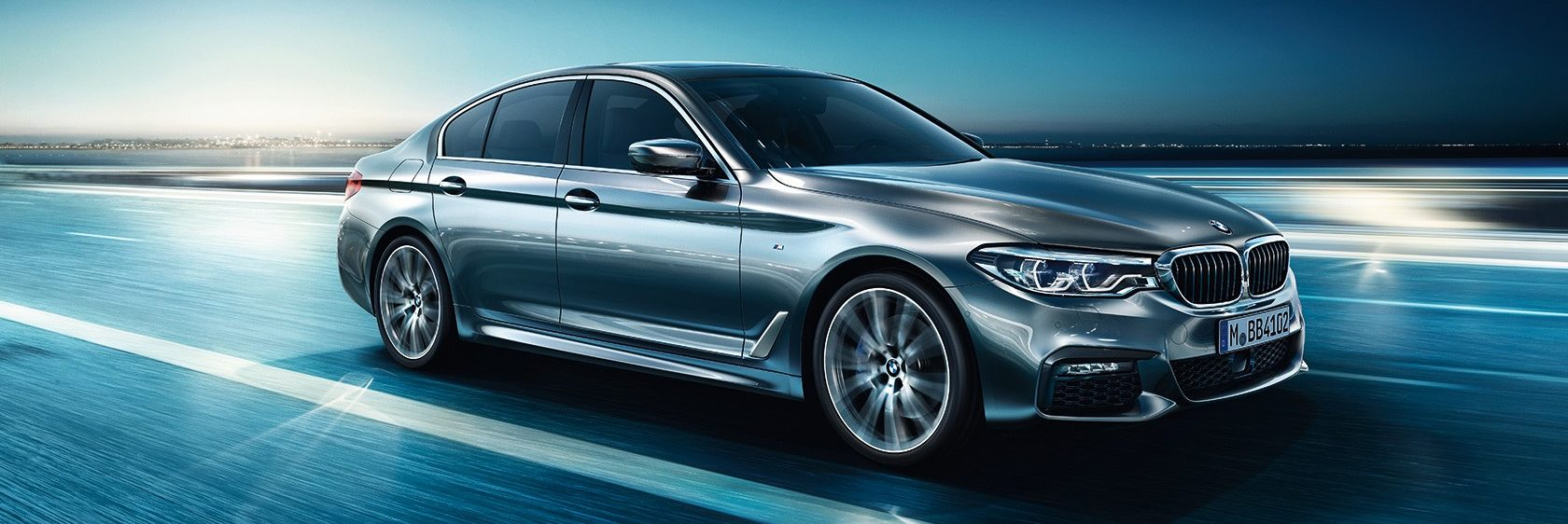 BMW 5 Series driving on a futuristic open road