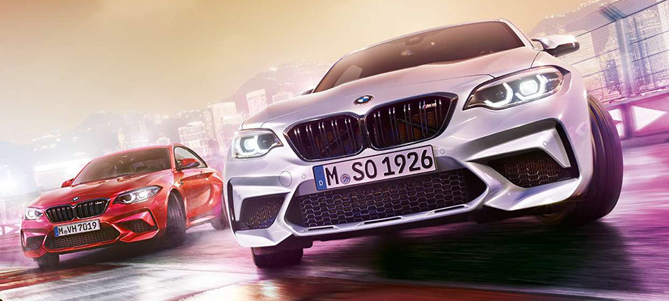 Two BMW M2 Coupe are drifting on race track with city lights background