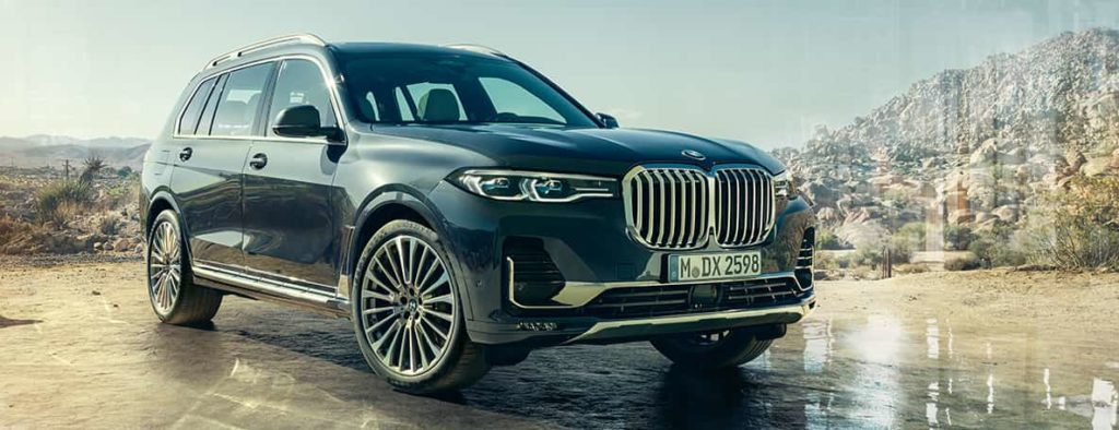 BMW X7 exterior: three-quarters front view in front of desert background