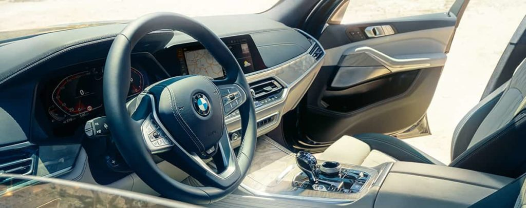 BMW X7 interior: view from the outside into the first row of seats with a view of the steering wheel, instrument cluster and leather seats