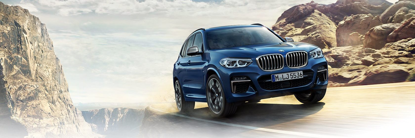 BMW X3 on the edge of a road by a mountain
