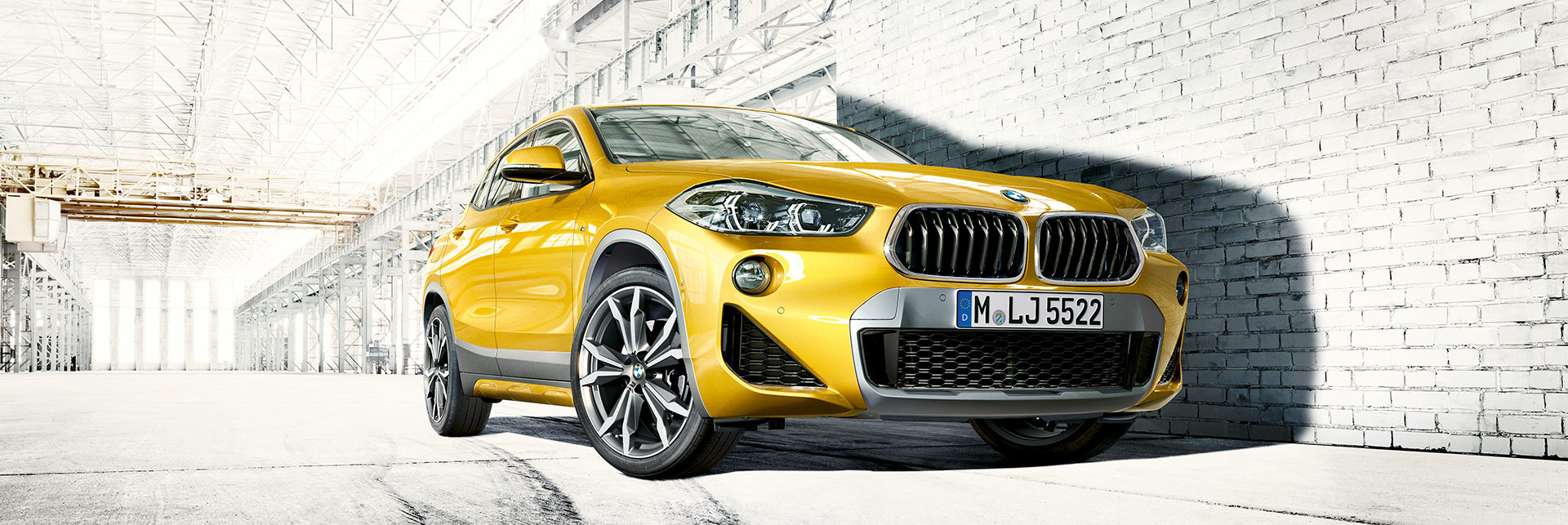 BMW X2 next to a modern white brick wall in a warehouse