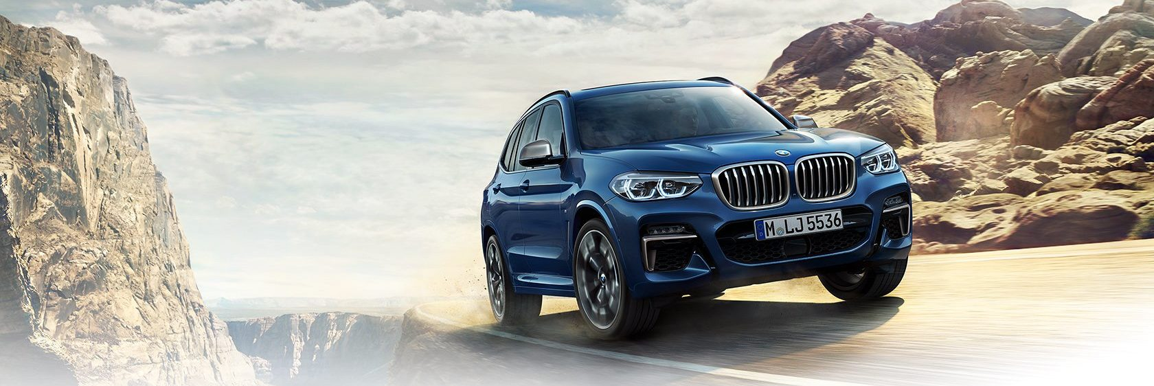 BMW X3 driving on a road near the edge of a cliff