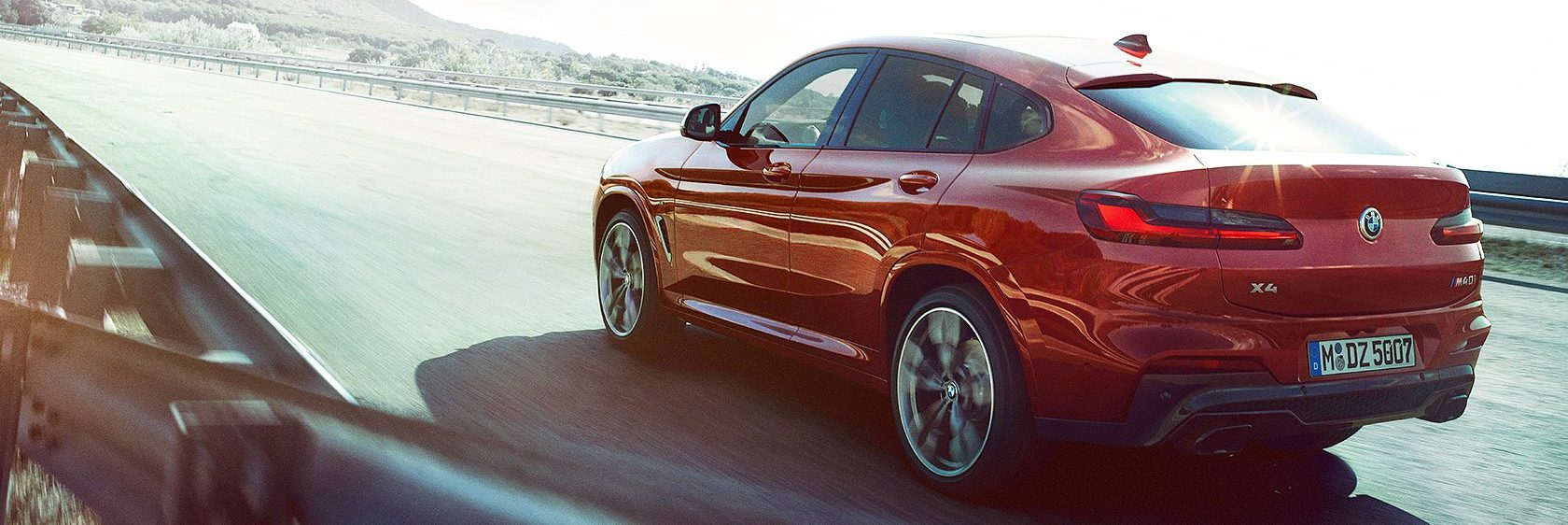 BMW X4 driving on country highway