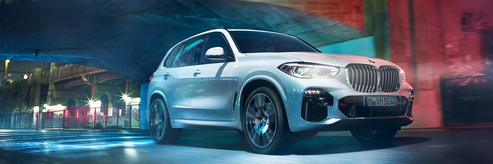 BMW X5 driving at night under a bridge in the city