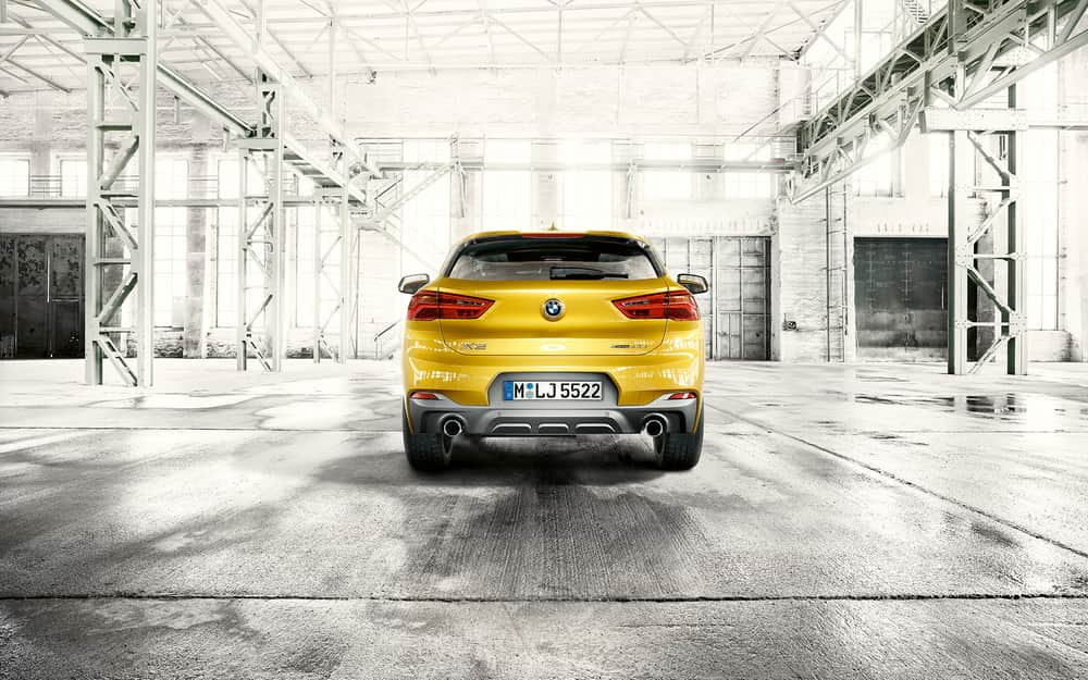 2020 BMW X2 in yellow facing away from the camera in an empty white warehouse
