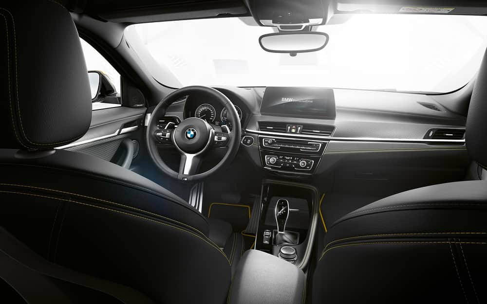 The black all-leather interior of the 2020 BMW X2 with the light shining inside from the windshield