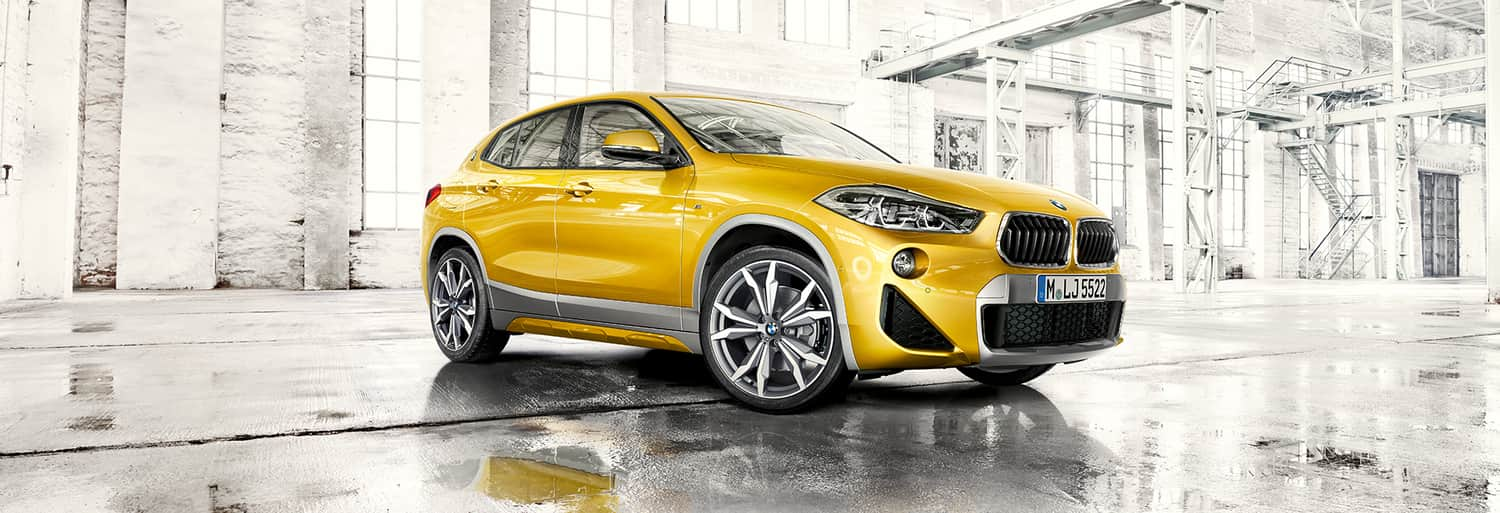 2020 BMW X2 in yellow facing angled right side profile from the camera in an empty white warehouse