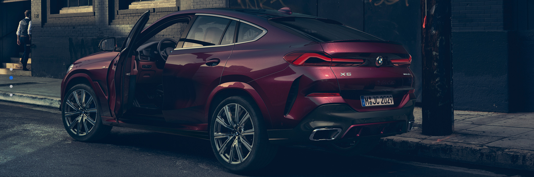 2020 BMW X6 shown in red parked on street with drivers door open