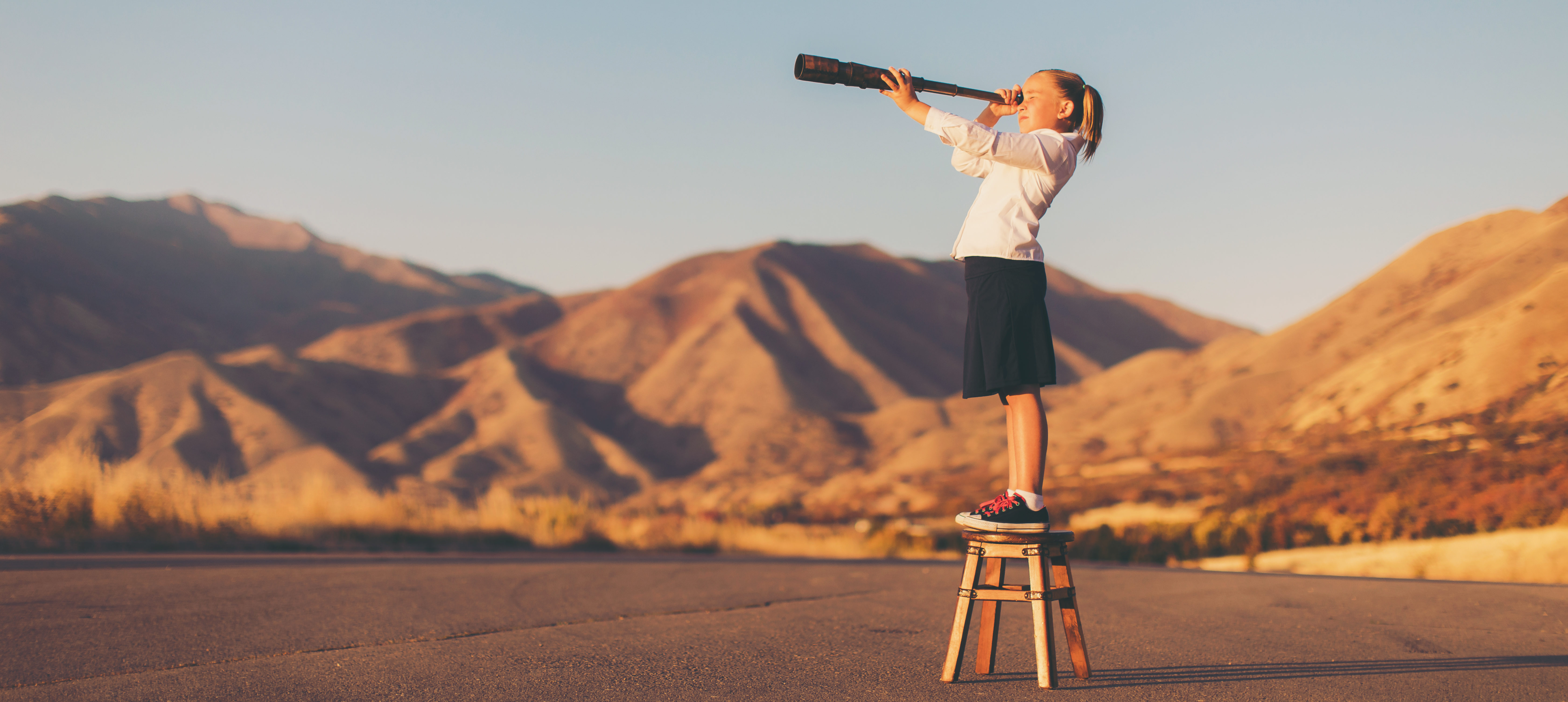A young girl standing on a stool looking through a telescope.