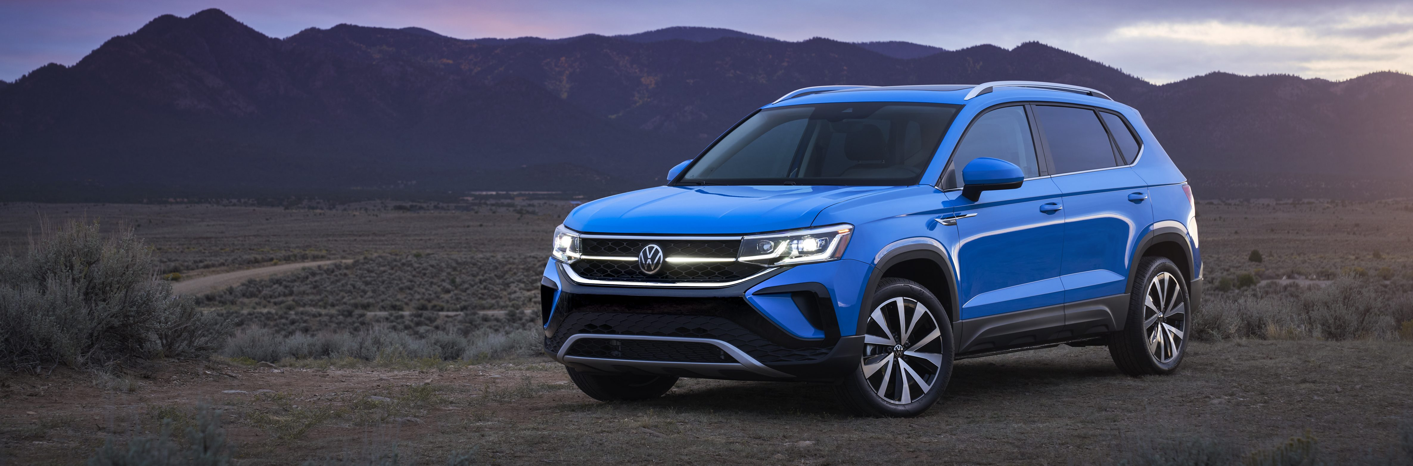 Blue 2022 Volkswagen Taos SUV In Front Of Mountain Background