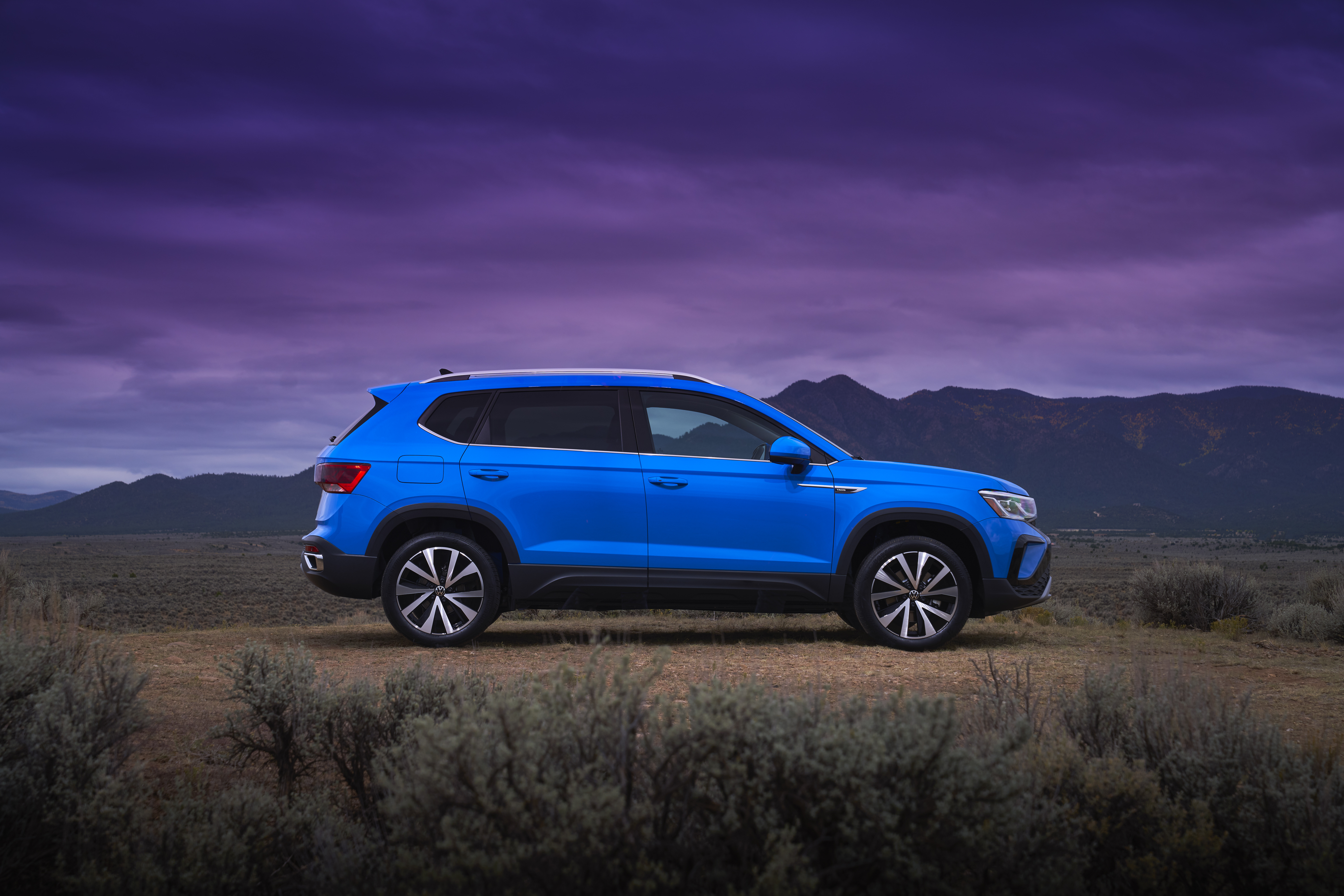 Side View of Blue 2022 Volkswagen Taos SUV with mountain and purple sky in background