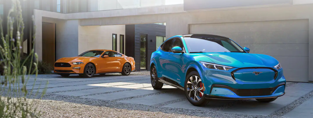 Two staggered 2021 Ford Mustang Mach-e models, one shown in electric blue and orange