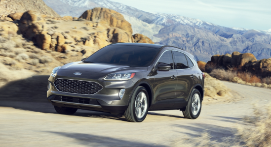 2020 Ford Escape driving on a country road by a big rock formation