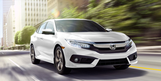 a White 2015 Honda Civic Sedan, driving in an urban city