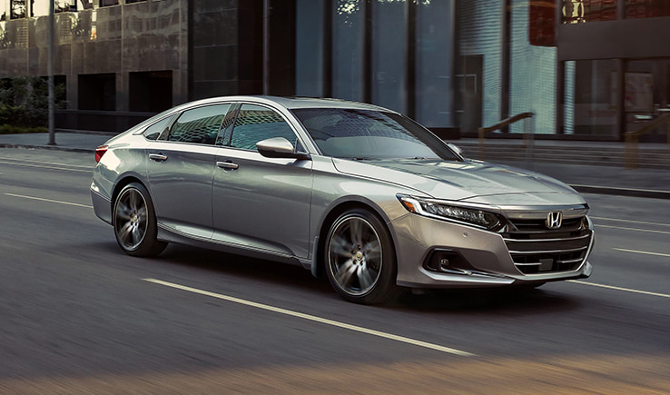 Front 3/4 exterior view of the 2021 Honda Accord sedan driving through the street