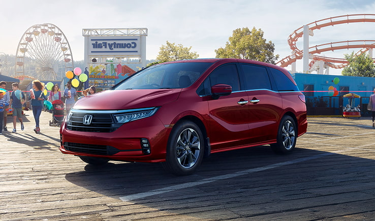 Side exterior view of the 2021 Honda Odyssey at a county fair parking lot