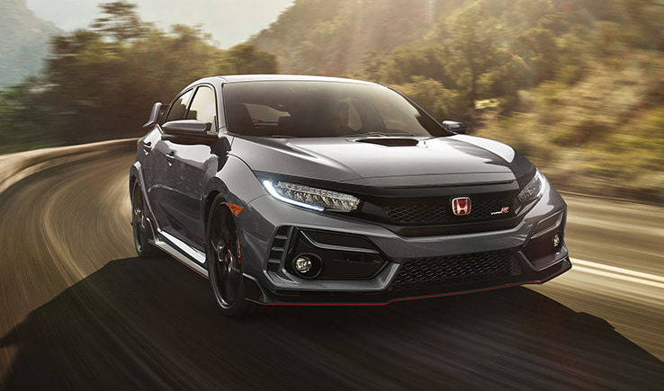 Front exterior view of the 2021 Honda Civic Type-R driving through a winding road