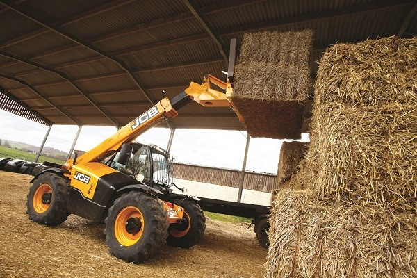 Side exterior view of a JCB machine loading a hay stack on top of a pile