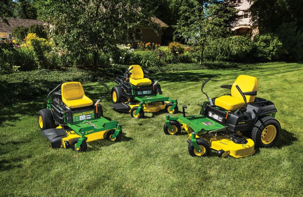Multiple John Deere equipment vehicles on display parked on the grass
