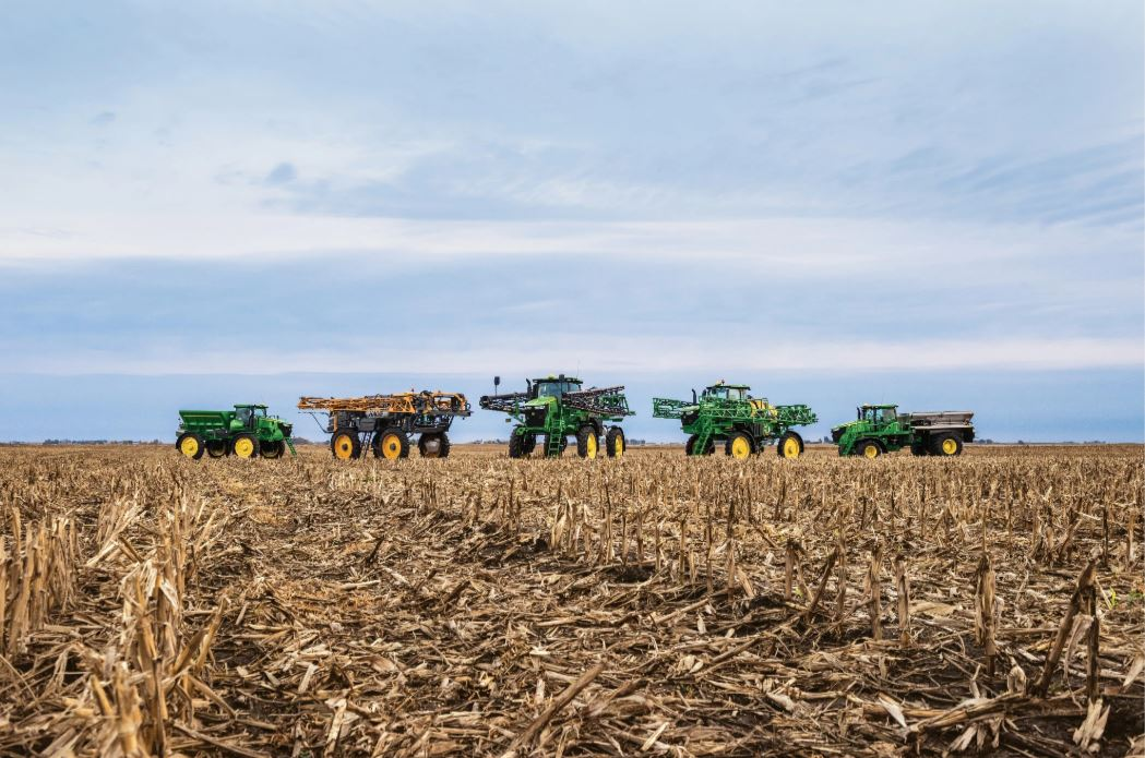 Multiple self-propelled sprayer machines parked next to each other on display