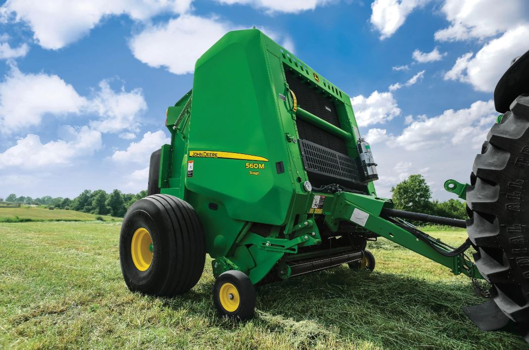 Exterior view of a baler machine attached to the back of a tractor