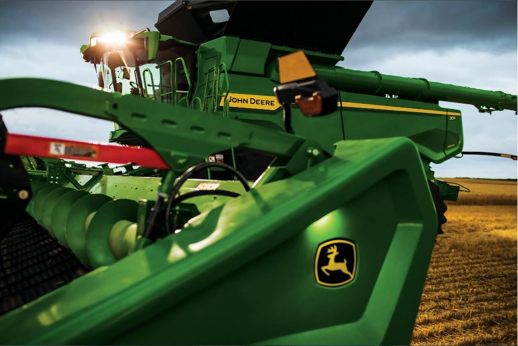 Side exterior view of the John Deere X9 driving through the farm land