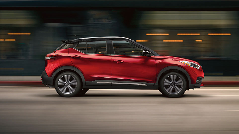 2018 KICKS passenger-side profile in Cayenne Red with Super Black roof. Nissan Kicks SR model shown with accessory spoiler.