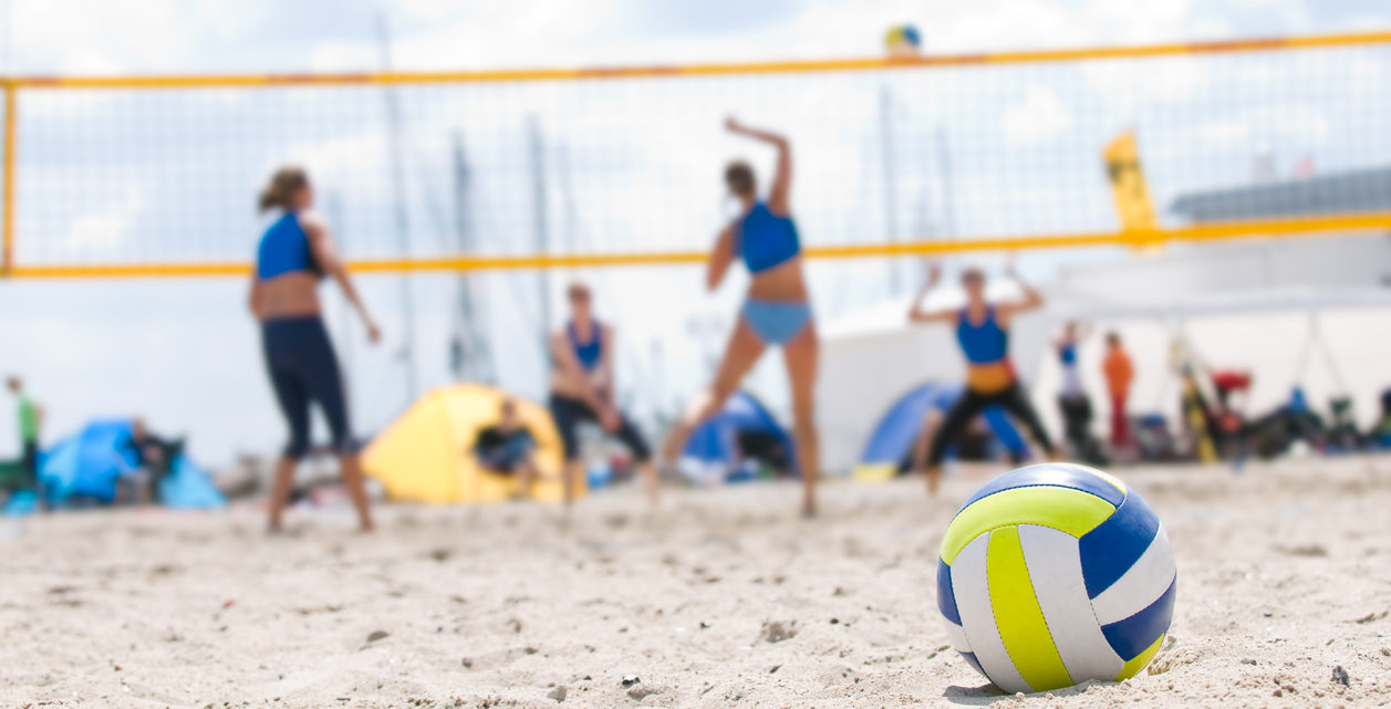 closeup of beach volleyball with game going on in the background