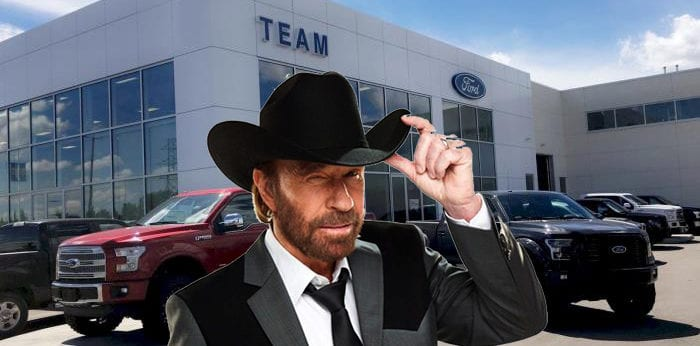Chuck Norris tipping his cowboy hat outside of team ford
