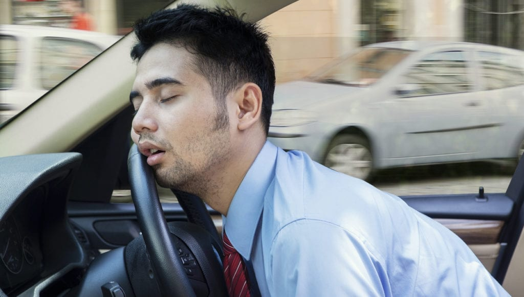 Exhausted young businessman sleeping in the car while driving the car on the road