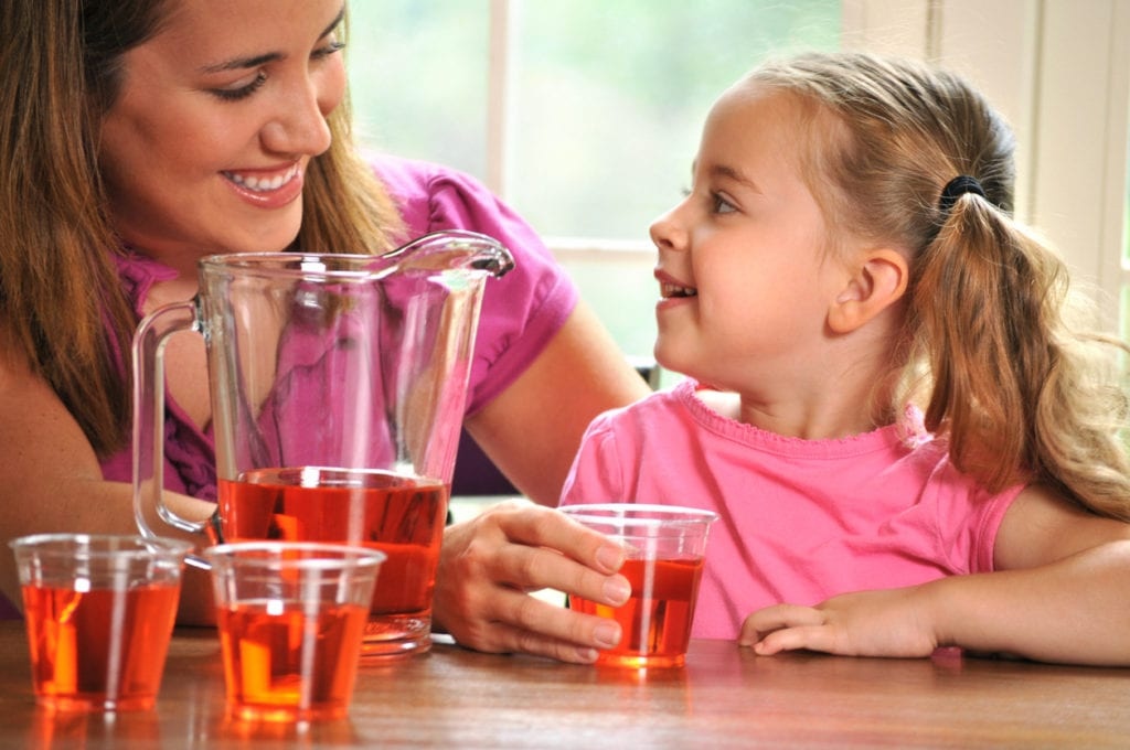 horizontal image of a young girl helping her mother with pouring drinks or juice, for a party or guests. the little girl has an enthusiastic expression. Focus in on the girl and a small amount of noise has been added to the background in post-processing.