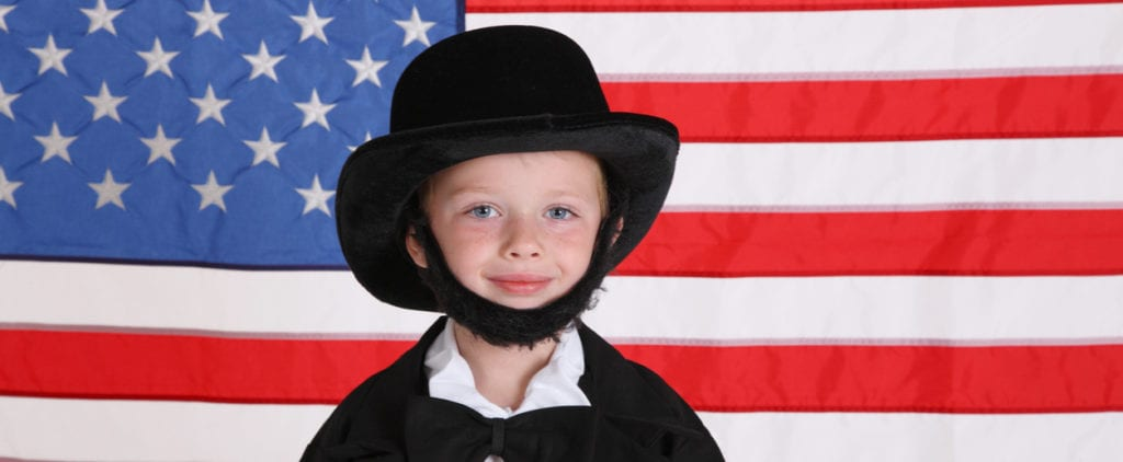 Young boy dressed up like Abraham Lincoln with American flag background