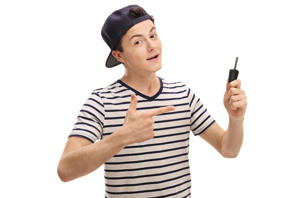 Happy teenage boy holding a car key and pointing isolated on white background