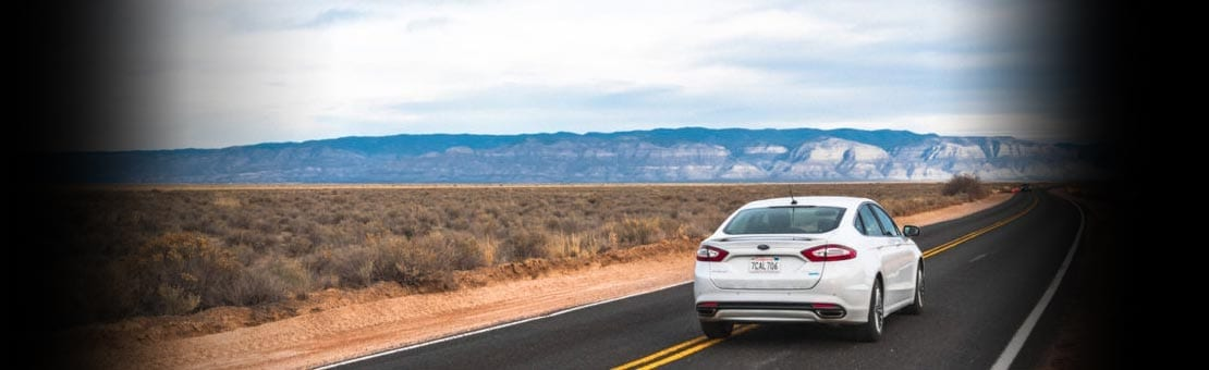 White Sands, NM, USA - February 17, 2014: White Ford Fusion driving on highway through desert in New Mexico.