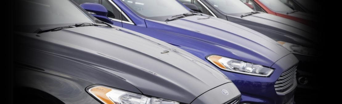 Dartmouth, Nova Scotia, Canada - February 23, 2014: New Ford Fusion vehicles of multiple colors in a row at a car dealership showing front fascia of each vehicle.