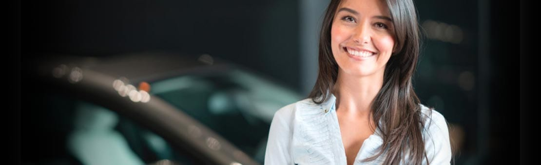 Portrait of a happy Latin American woman buying a car at the dealership