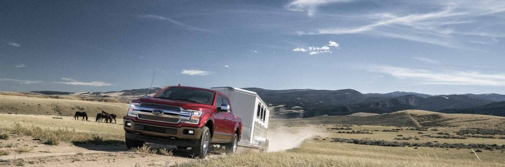 ruby red ford f-150 towing a trailer through the prairies