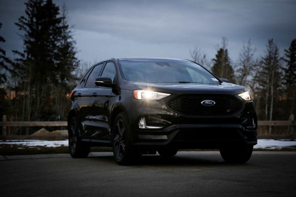 low front quarter shot of the 2019 Ford Edge ST in Agate black  in the dark