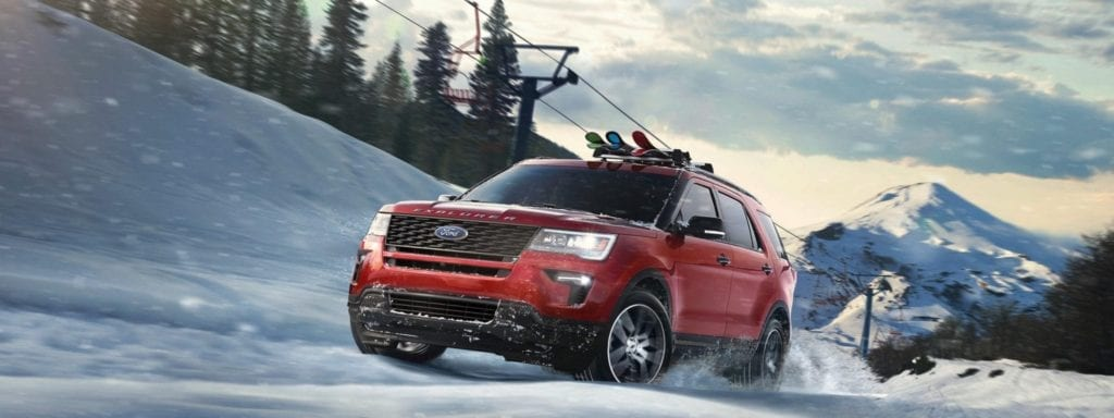red ford explorer driving on snowy mountain