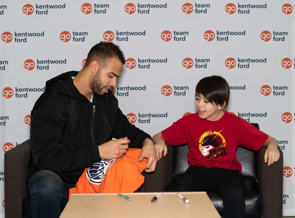 Edmonton Oilers defenseman Darnell Nurse signs an autograph for a young fan in a red shirt