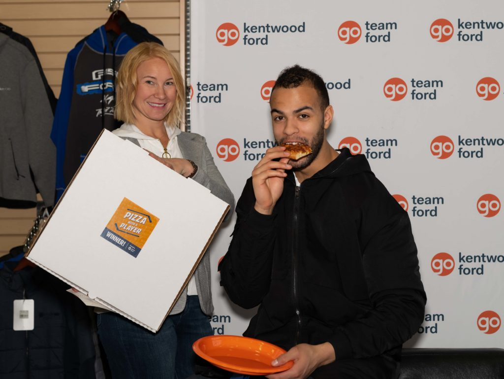 A blonde woman with a prize box stands next to Edmonton Oilers defenseman Darnell Nurse as he eats a slice of pizza off an orange plate