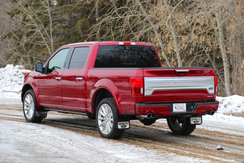 A three-quarter rear view of a red Ford F-150 Limited, parked on a snow covered country lane